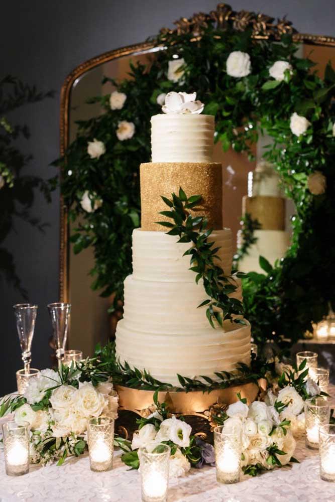 As flores chamadas de copo de leite são as mais usadas na decoração de casamento. Nesse caso, o arranjo de flores foi colocado na mesa do bolo junto com alguns copos com velas.