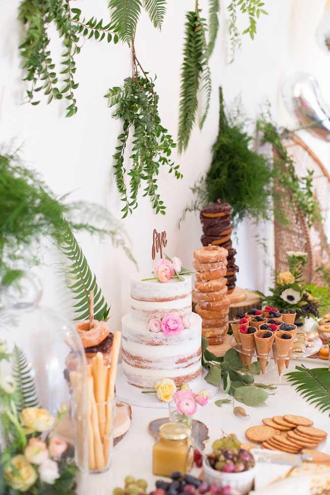 Essa mesa linda de guloseimas traz um bolo espatulado no centro, uma torre de donuts e pequenas frutas, como mirtilos, amoras, uvas e framboesas; para completar a decoração um jardim vertical na parede