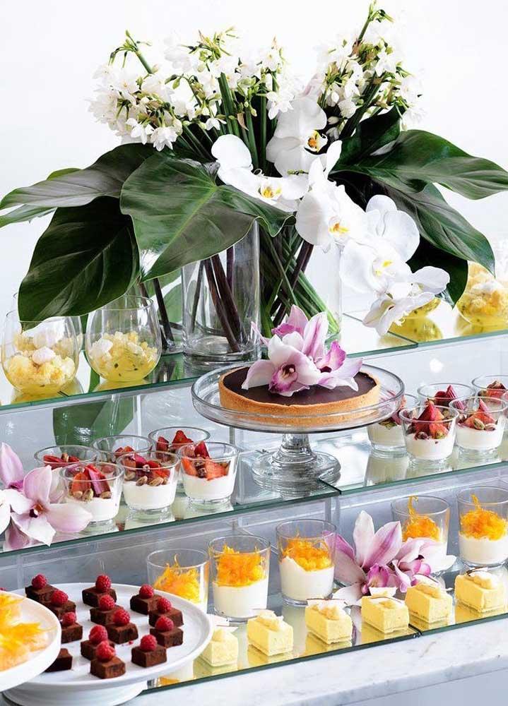 As prateleiras de vidro reforçam a proposta elegante dessa mesa de guloseimas