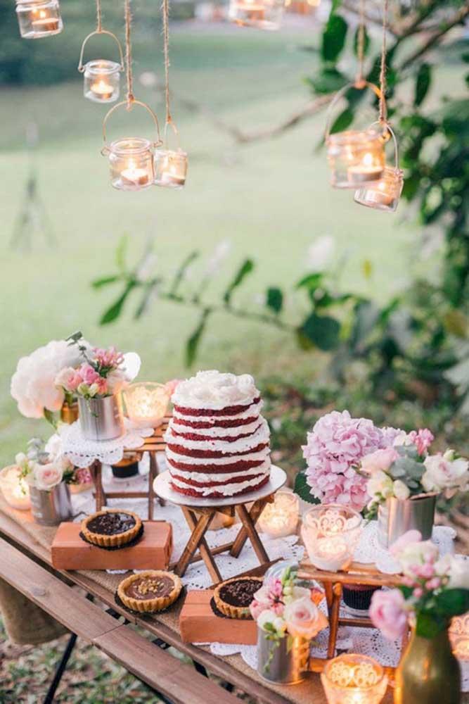 Ao ar livre, a mesa de guloseimas fica mais bonita quando decorada com flores e lanternas