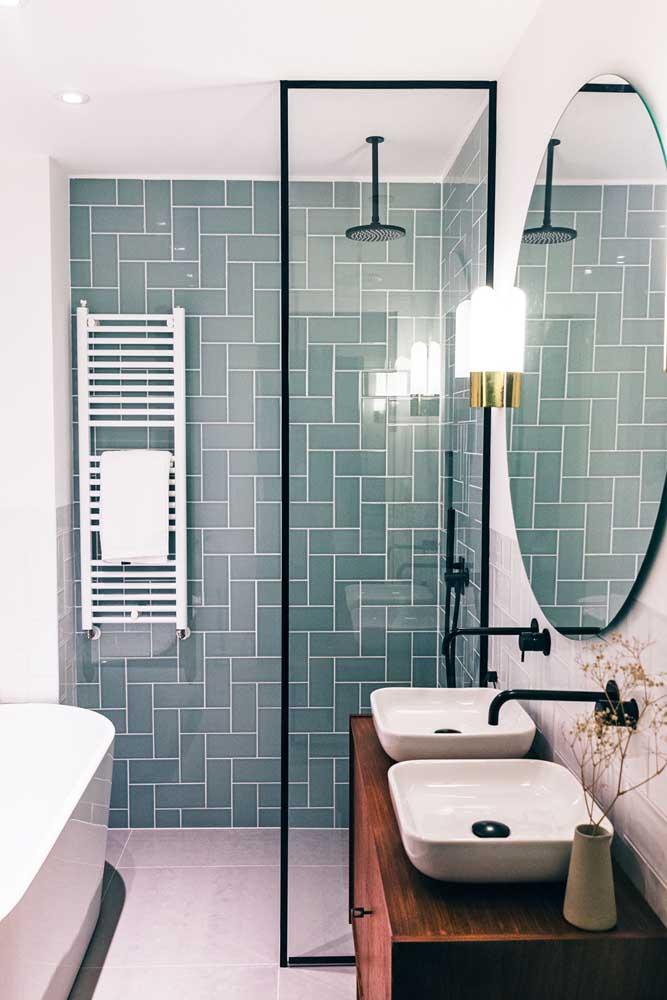 Esse banheiro pequeno apostou em metais pretos e em um revestimento de cor diferenciada para área do box; a bancada de madeira rústica fechou a proposta