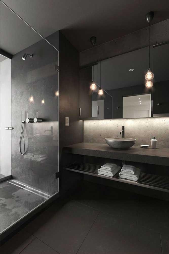 E reforce a iluminação indireta, como esse banheiro da imagem que apostou em luminárias pendentes sobre o espelho e fitas de LED atrás do espelho