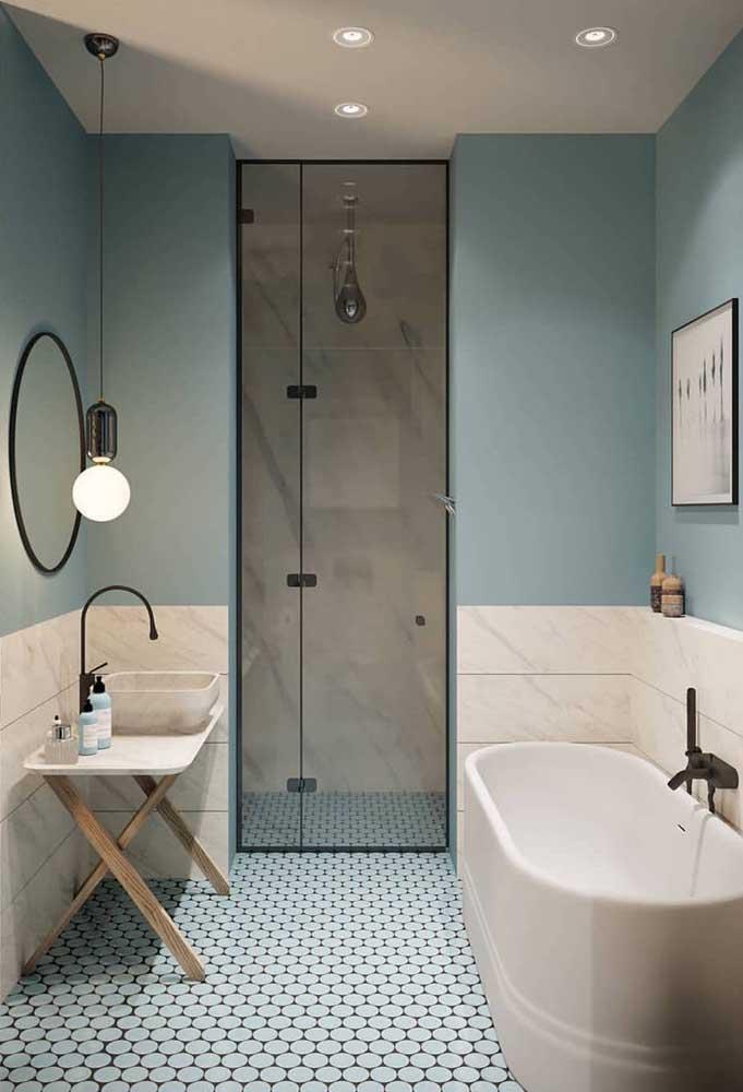 Modelo de banheiro simples, pequeno e minimalista; o destaque fica para a parede meio a meio