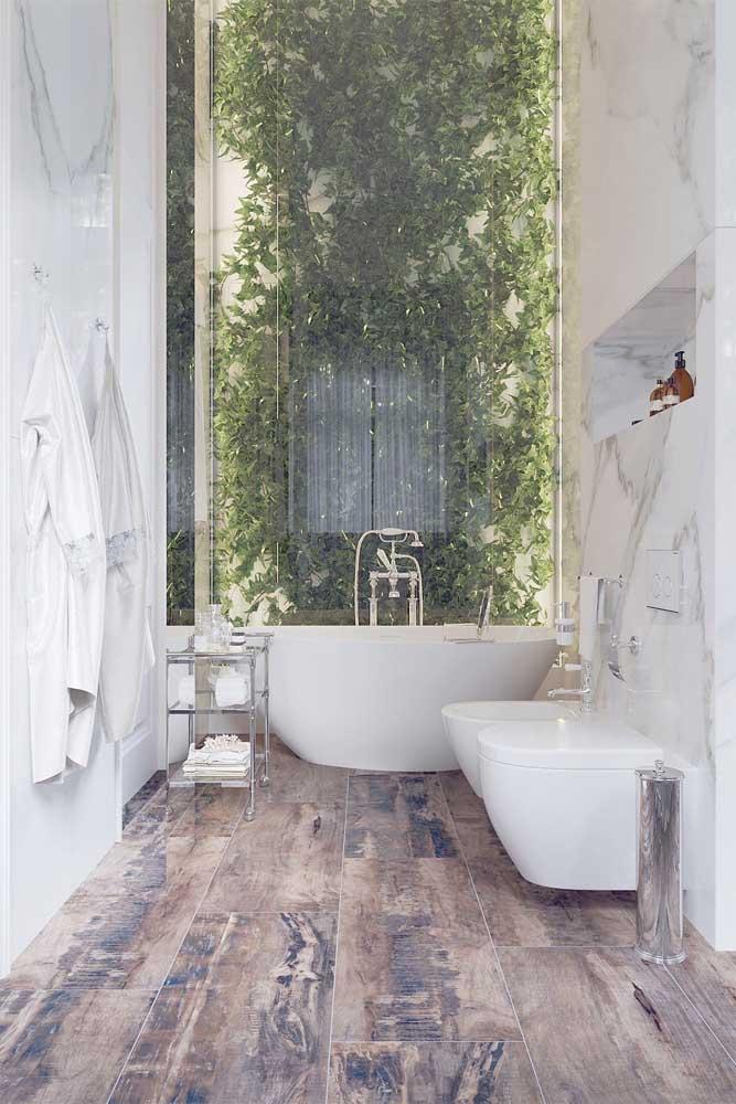 Modelo de banheiro com pé direito alto, o jardim vertical ao fundo, limitado pela parede de vidro, é o grande destaque do projeto
