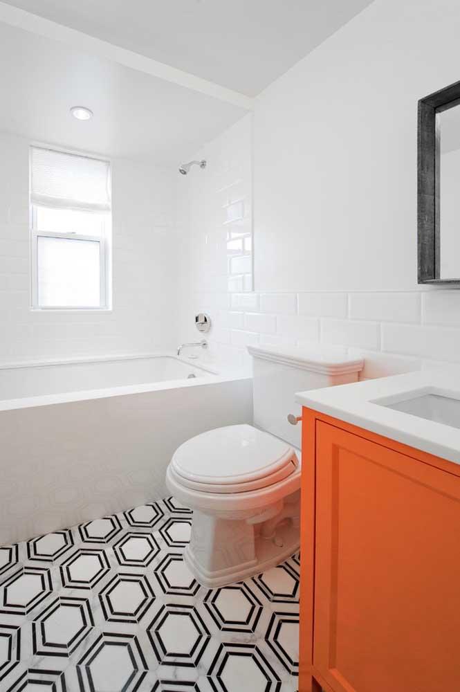 O piso geométrico preto e branco pede por uma base clara e neutra; o armário laranja confirma a intenção retro desse banheiro