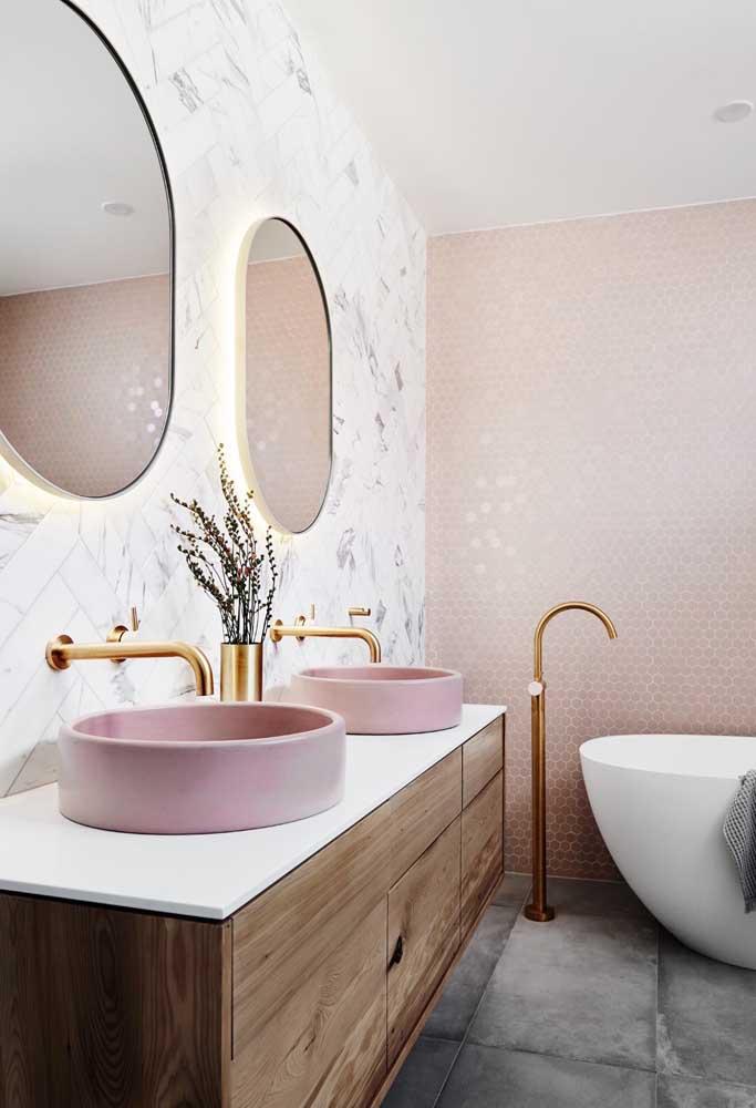 Banheiro com bancada dupla decorado com metais dourados e um discreto e suave cor de rosa