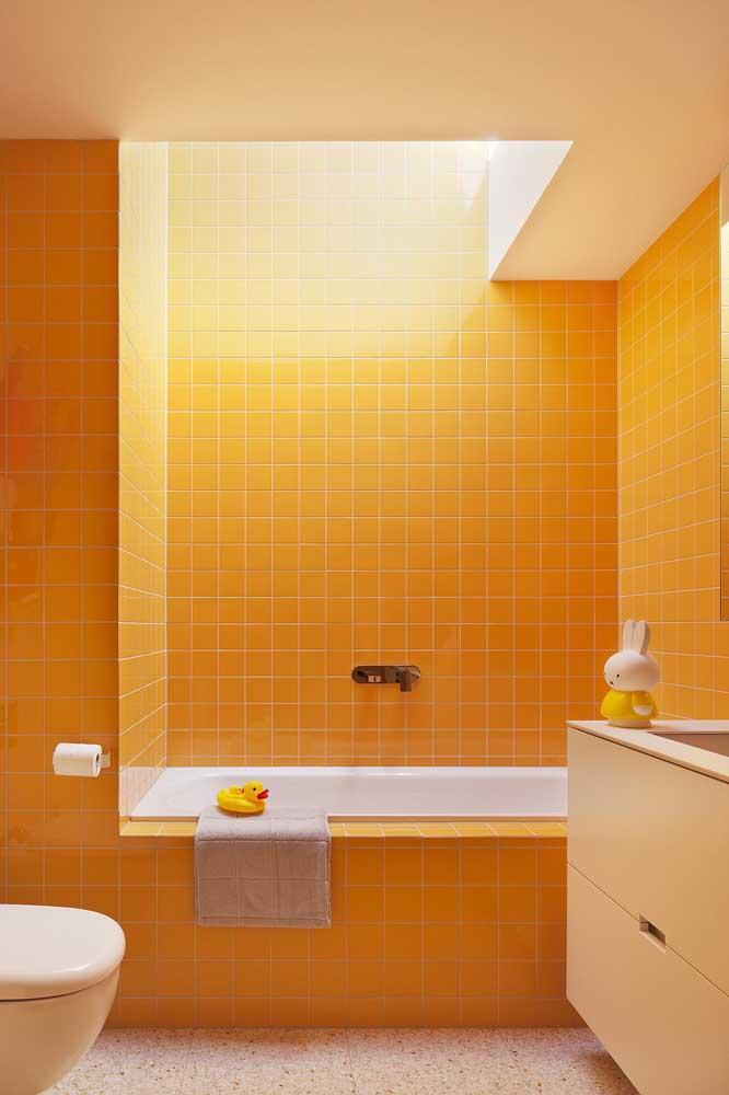 O laranja das pastilhas aquece e dá animo a esse banheiro simples