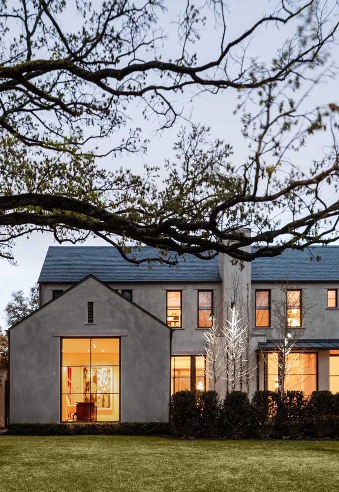 Casa ampla, espaçosa com destaque para as grandes janelas de vidro e revestimento de cimento queimado; o jardim na frente completa a fachada