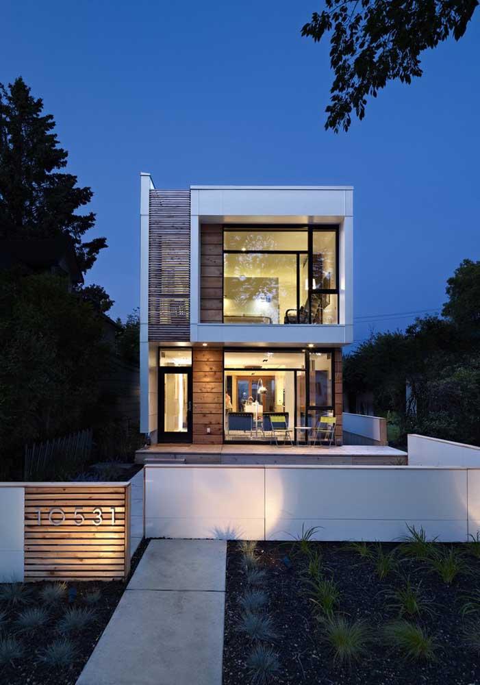 Os detalhes em preto dessa fachada formam um belo e discreto contraste com as paredes brancas e a madeira do revestimento