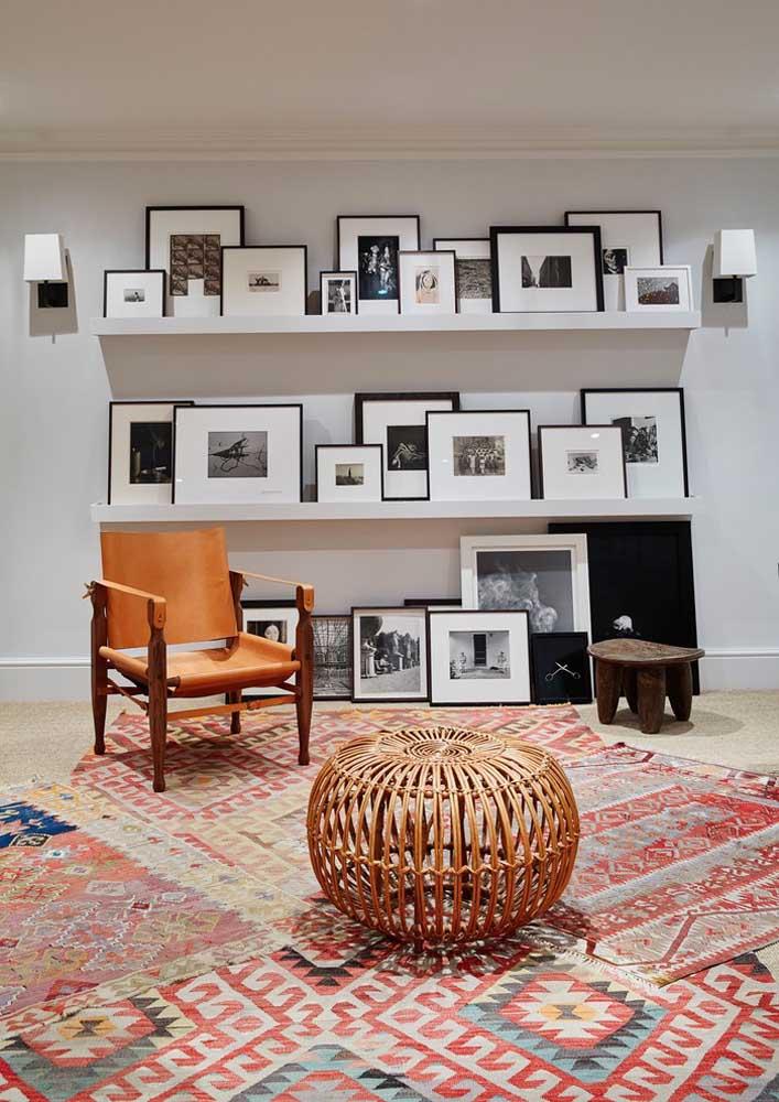 Que tal organizar seus quadros com fotos em prateleiras? Se não couberem todos, você pode seguir a decoração no piso.