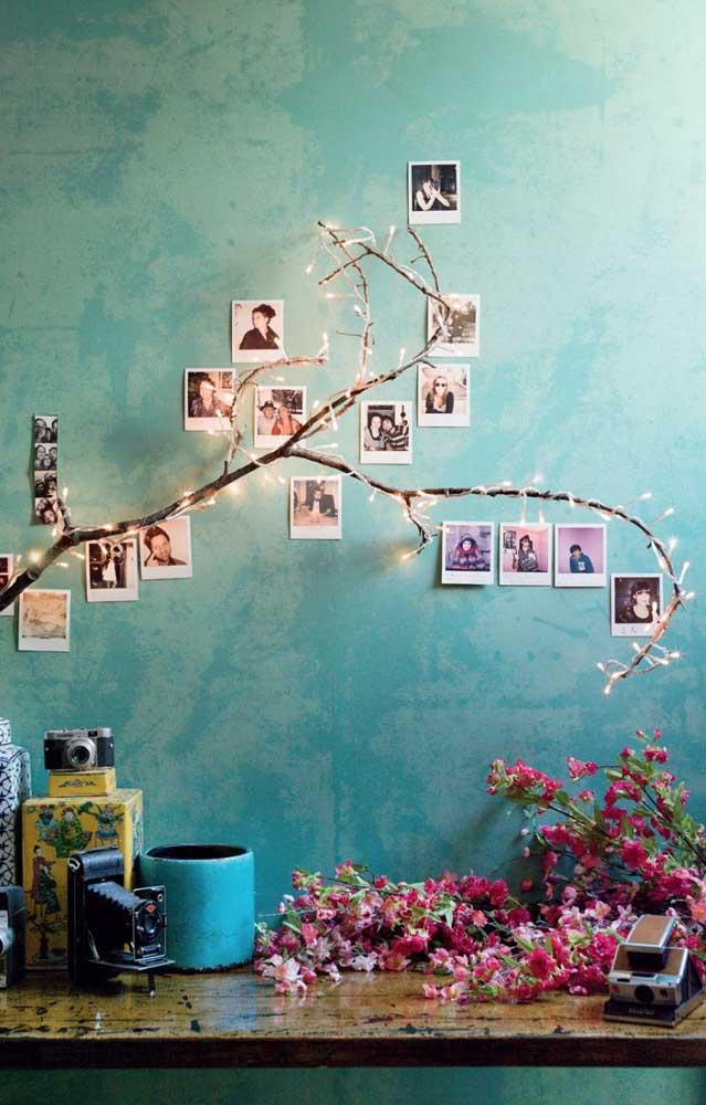 Se você quer algo mais romântico ou feminino, cole as fotos na parede seguindo a mesma direção do galho com luzes.