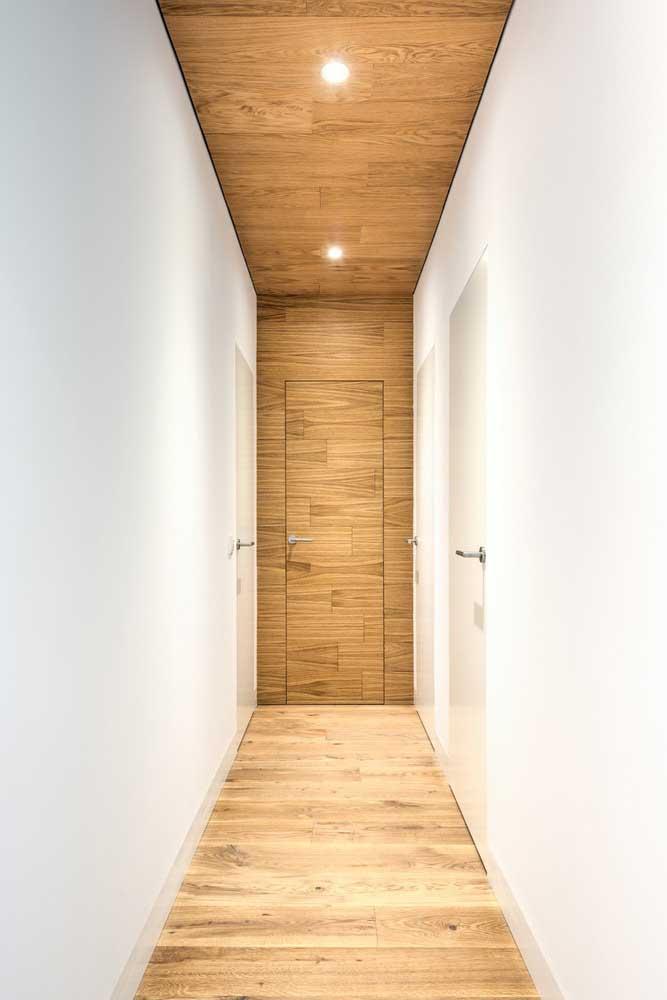 Piso vinílico amadeirado para o corredor clean que também apostou no uso da madeira na porta e no teto