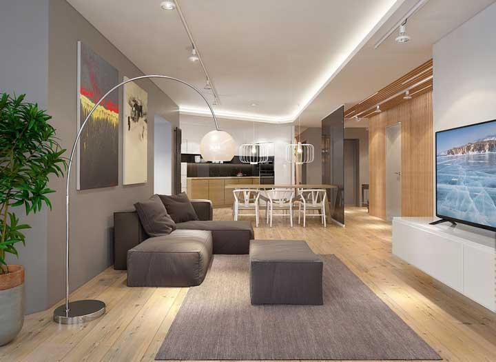 Sala de estar integrada à cozinha com piso vinílico em tom de madeira natural
