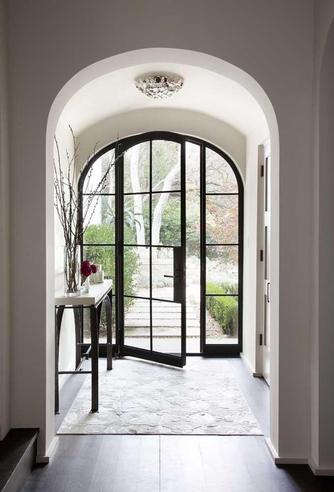 Porta de vidro na entrada da casa com moldura em ferro