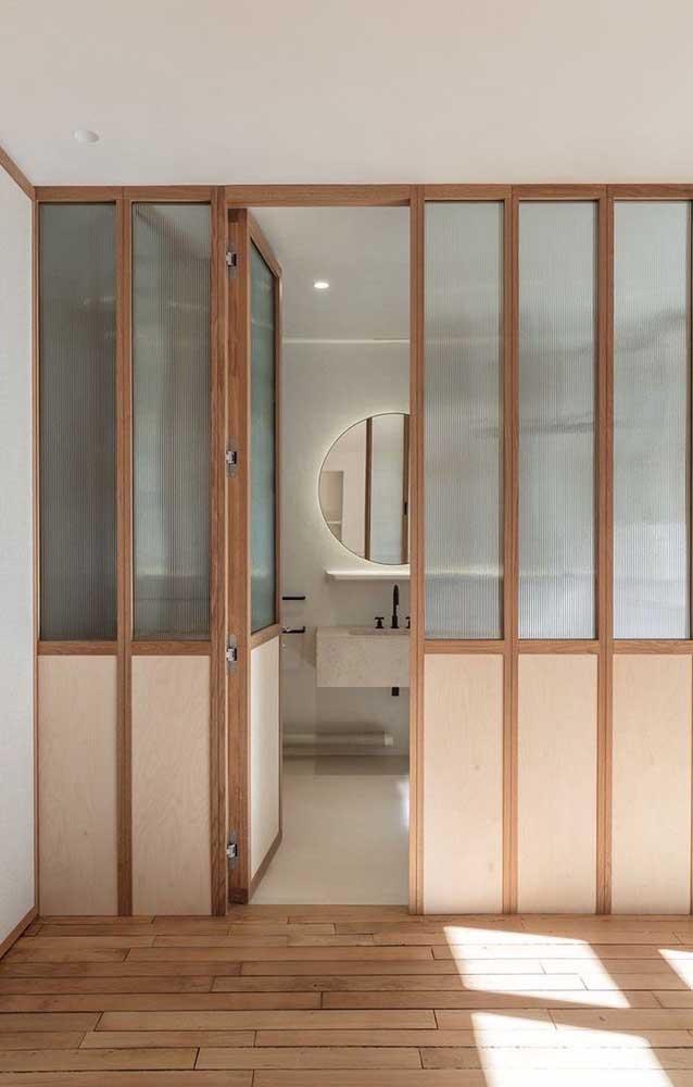 Porta de vidro canelado, com detalhes em madeira para o banheiro