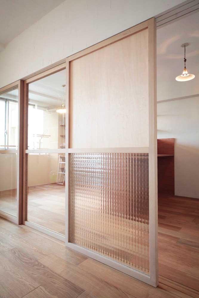 A porta de correr em vidro e madeira traz detalhes que garantem a privacidade