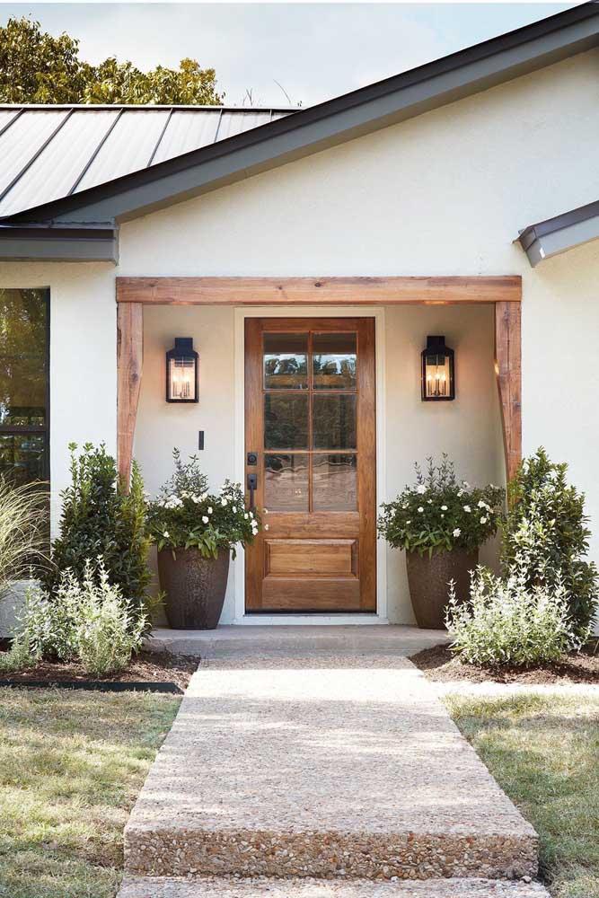 A porta de madeira com detalhes em vidro na entrada da casa garante a vista para o jardim; para quem olha de fora, o visual é o de uma fachada acolhedora e aconchegante