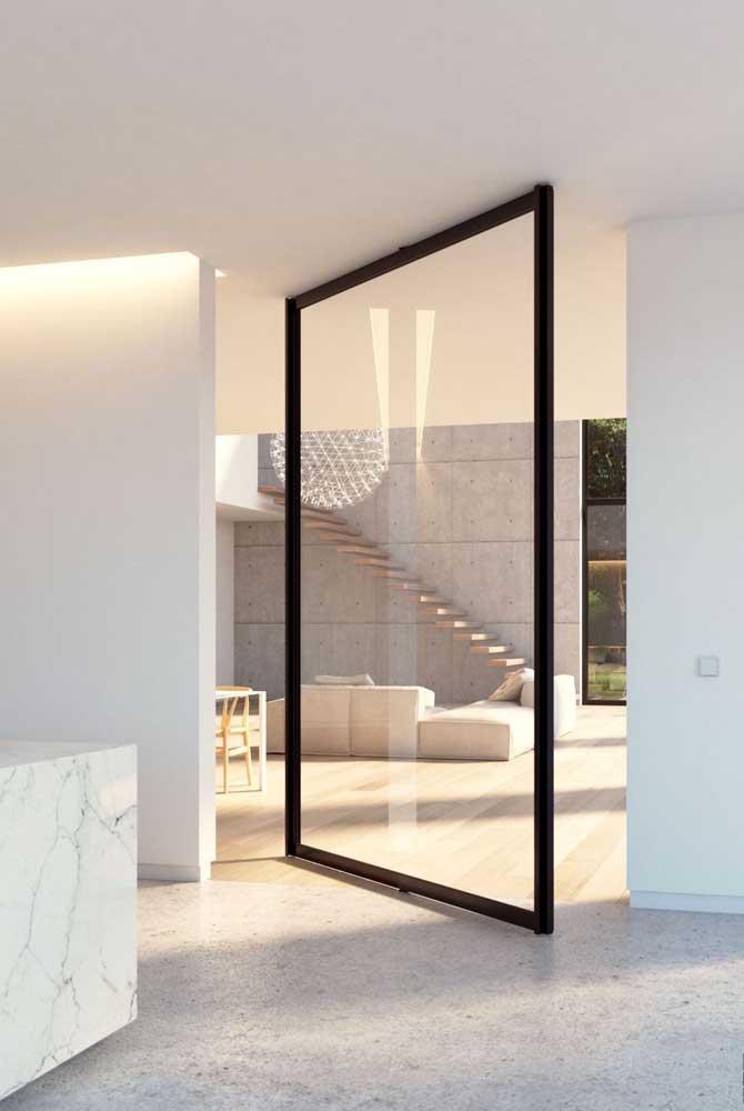 Com design clean, a porta de vidro pivotante integra totalmente os ambientes e favorece a entrada de luz natural no espaço