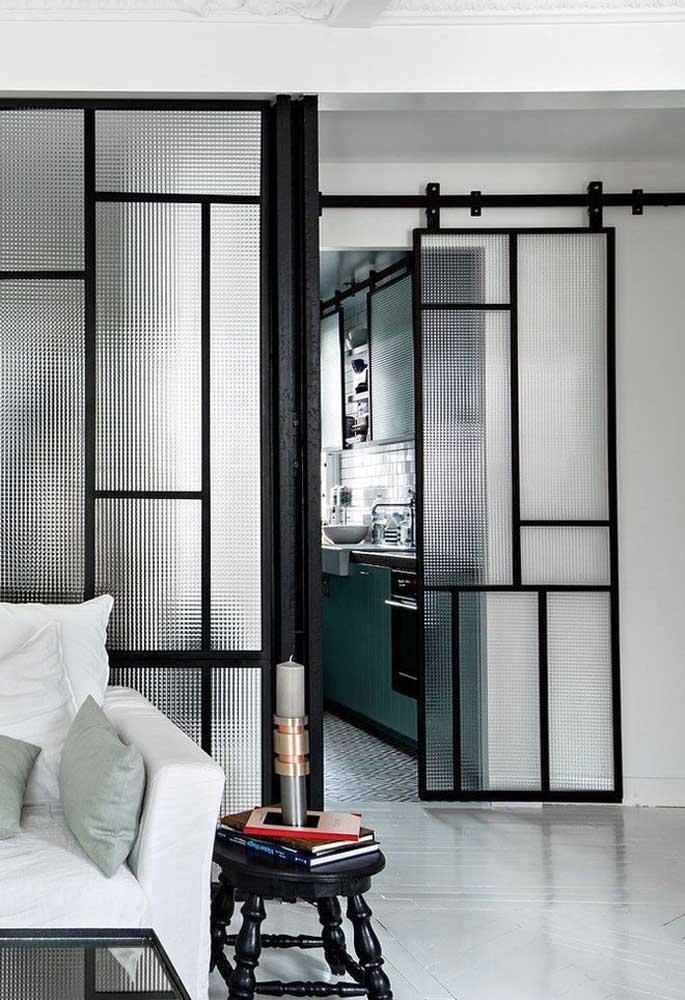Porta de vidro de correr com acabamento pontilhado e ornamental; a moldura preta confere modernidade ao ambiente