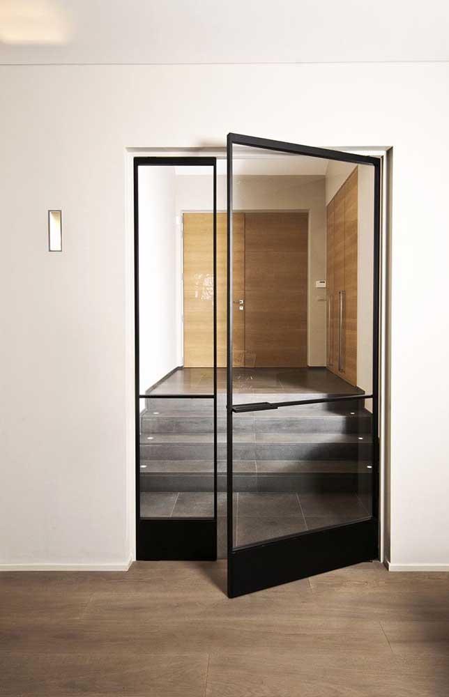 Porta de entrada em vidro, com moldura em ferro, contrastando com os detalhes do ambiente em madeira