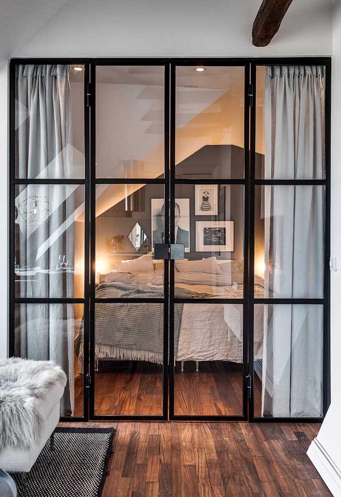 O quarto de design industrial ganha integração com outros ambientes pela porta de vidro de estilo moderno