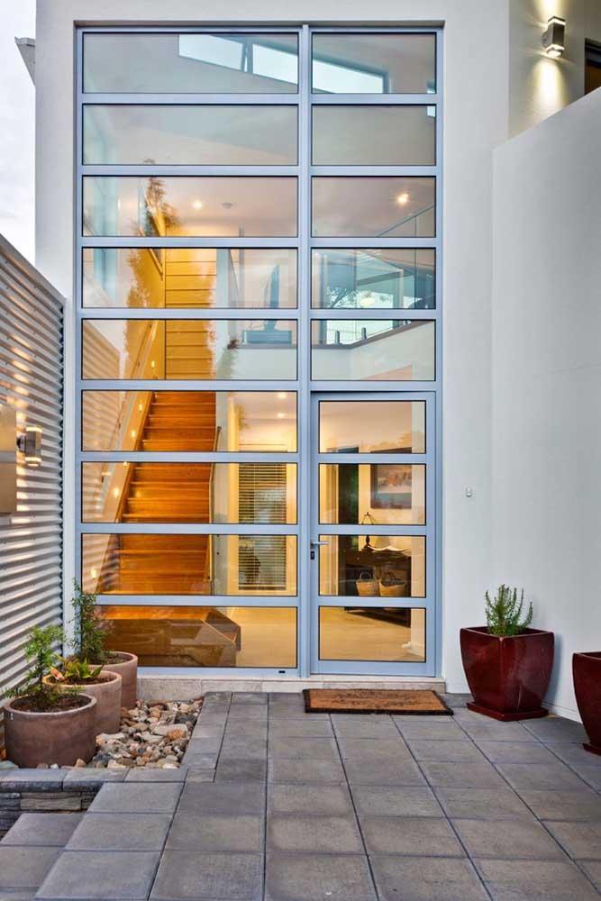 A casa com pé direito alto conta com uma porta e parede de vidro com moldura em ferro com vista para o hall de entrada
