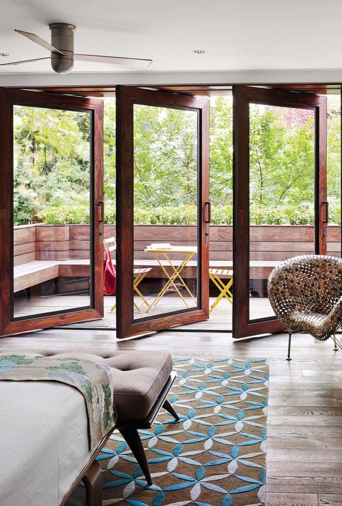 Três portas pivotantes de vidro formam o acesso entre a sala e a varanda