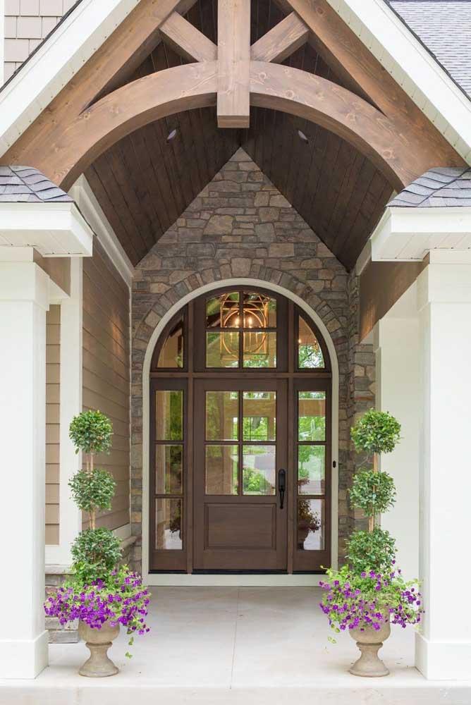 Aqui, a porta de vidro com moldura em madeira cria um bonito e rústico contraste com a parede de pedras