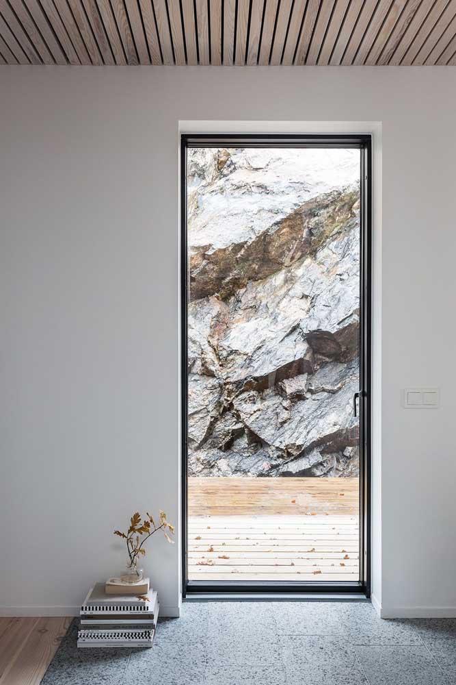 Porta de vidro em folha única tradicional aumentando a entrada de luz natural no ambiente e favorecendo a contemplação da vista que vem de fora