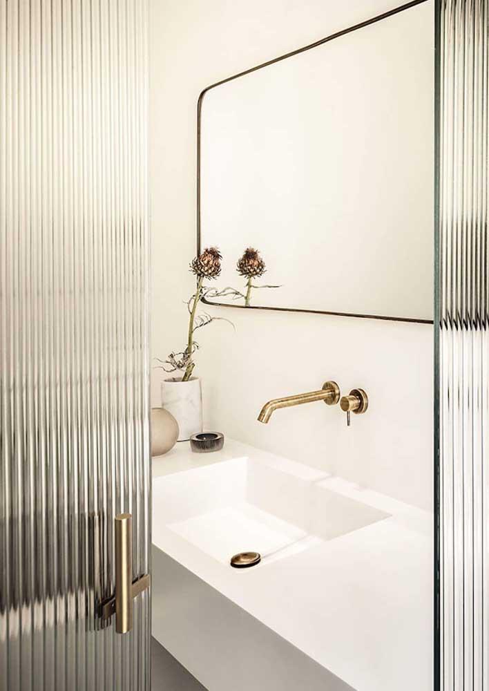 Porta de vidro canelado para banheiro; o puxador dourado dá o toque final ao visual da porta