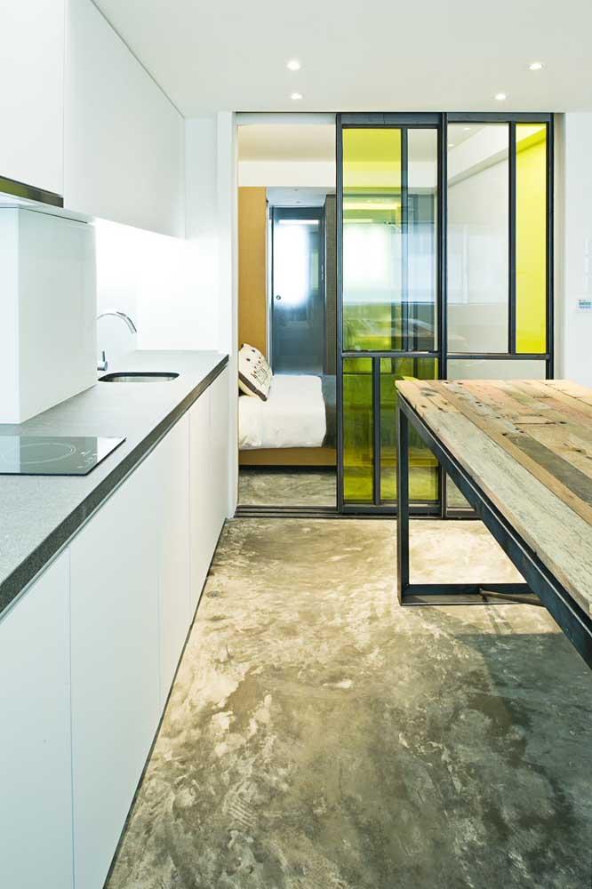 A porta de vidro colorido integra a cozinha ao quarto; vale destacar que a porta aqui cria um isolamento acústico, além de evitar a propagação de odores para outros ambientes