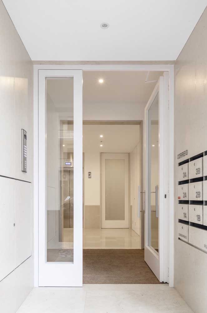 Porta de vidro em prédio empresarial, com moldura em madeira branca; um clássico