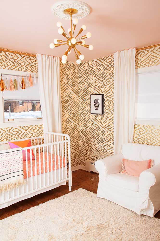 Que tal combinar a textura do papel de parede com as cores da luminária? Nesse caso, a cor dourada é o grande destaque da decoração.