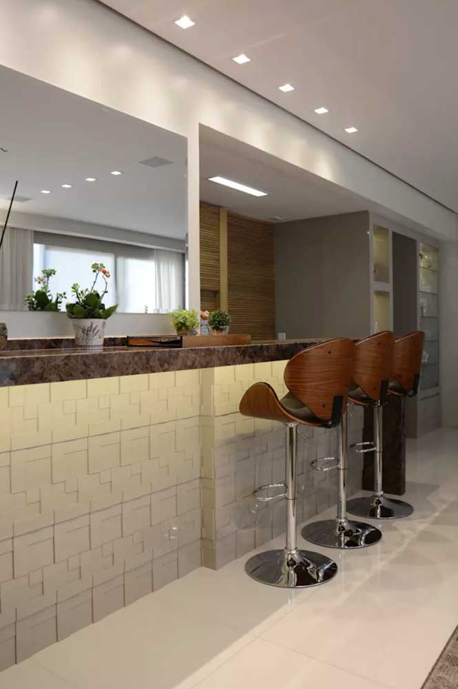 A opção pelo revestimento 3D no balcão da cozinha torna este espaço muito mais aconchegante e moderno