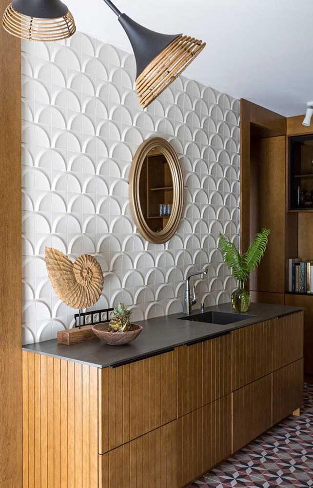 Revestimento 3D na parede e piso geométrico no chão: apesar da carga visual, o banheiro não perde em harmonia