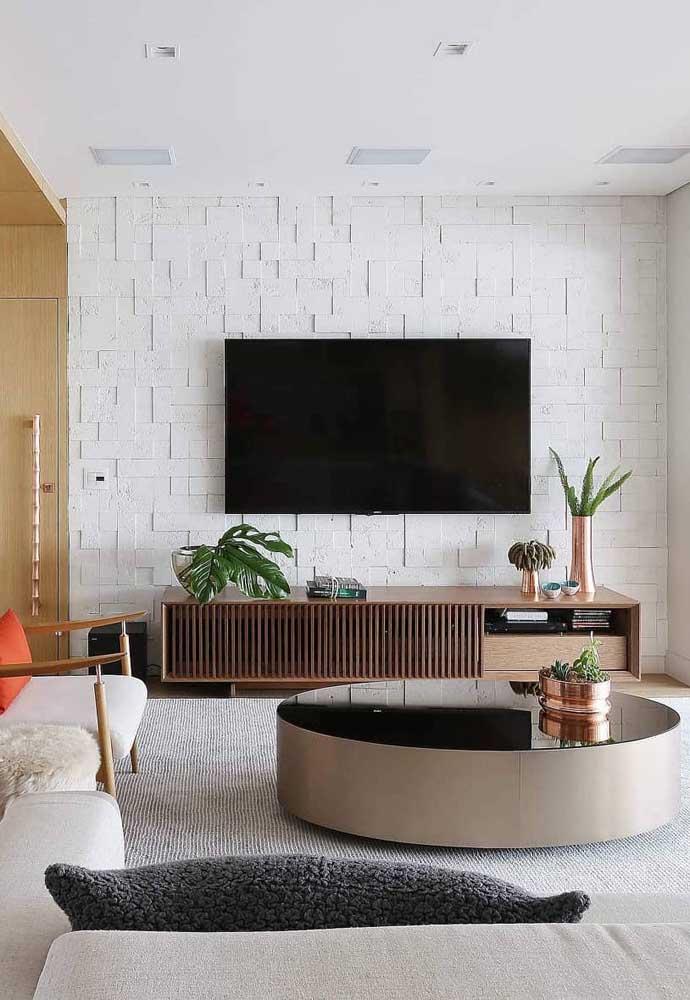 A parede em 3D funciona como um painel elegante para a TV