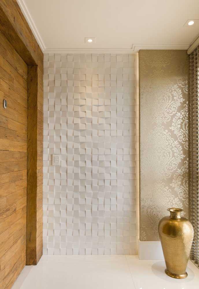 No hall de entrada, o revestimento branco abre espaço para que os detalhes em dourado se sobressaiam