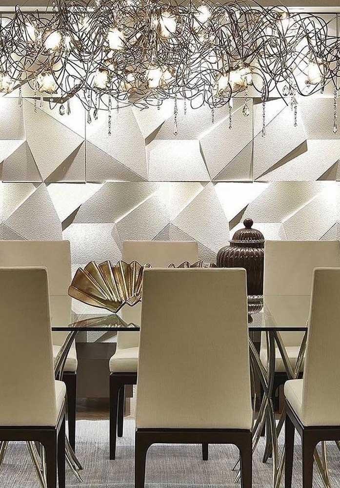 Parede branca não precisa ser monótona, basta adicionar efeitos tridimensionais nela; dessa forma os móveis de designer e o lustre também conseguem aparecer na decoração
