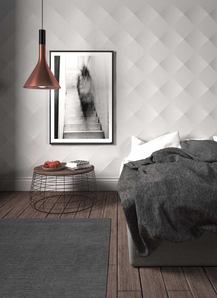 O quarto minimalista traz um revestimento 3D de pouca informação, mas ainda assim capaz de trazer profundidade e movimento a parede; o quadro complementa a decoração seguindo a mesma proposta