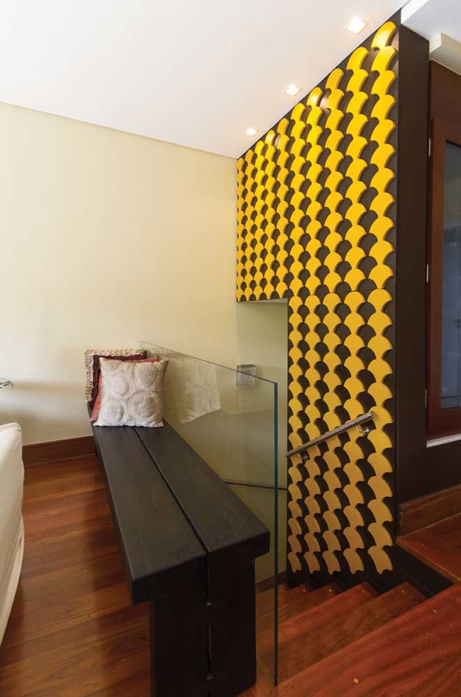 Não há quem passa imune por essa parede com revestimento 3D preto e amarelo; um destaque em qualquer ambiente