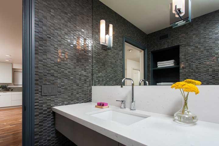 As luzes criam um efeito espelhado para o revestimento 3D cinza escuro desse banheiro