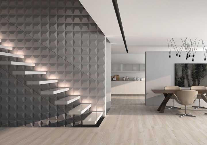 O moderno cinza entra aqui na composição da parede 3D; o guarda corpo de vidro em momento algum tira a soberania do revestimento