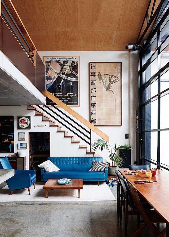 Nessa sala de estar, o design e a cor do sofá chamam bastante atenção. Para completar, foram usados quadros enormes para destacar a parede do ambiente.