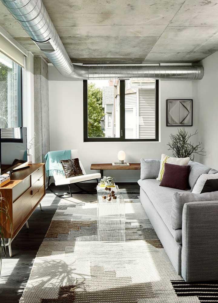 Os apartamentos no estilo industrial são perfeitos para fazer uma decoração moderna como a parede feita com cimento queimado.