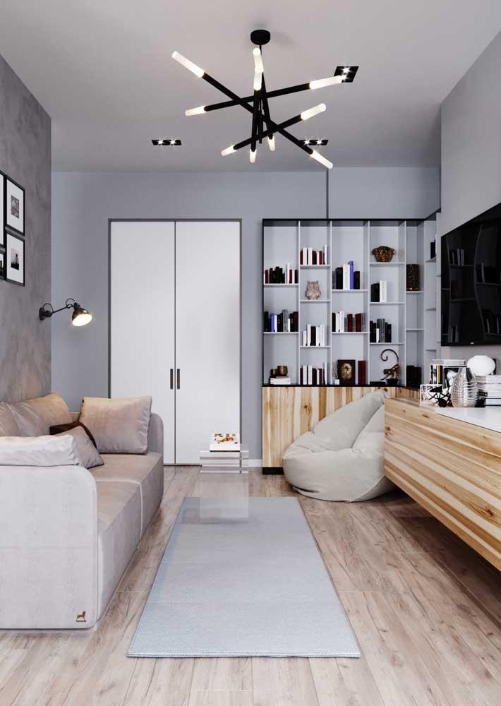 Uma luminária com design diferenciado é o grande destaque na decoração dessa sala de estar.