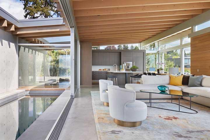 Cômodos abertos como esse modelo ficam perfeitos com móveis em tons mais claros. Para complementar, use algum elemento decorativo de madeira.