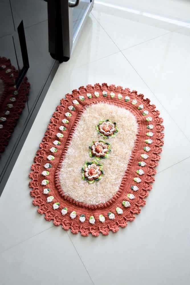 Destaque para o uso do fio barroco nesse tapete de crochê oval com flores