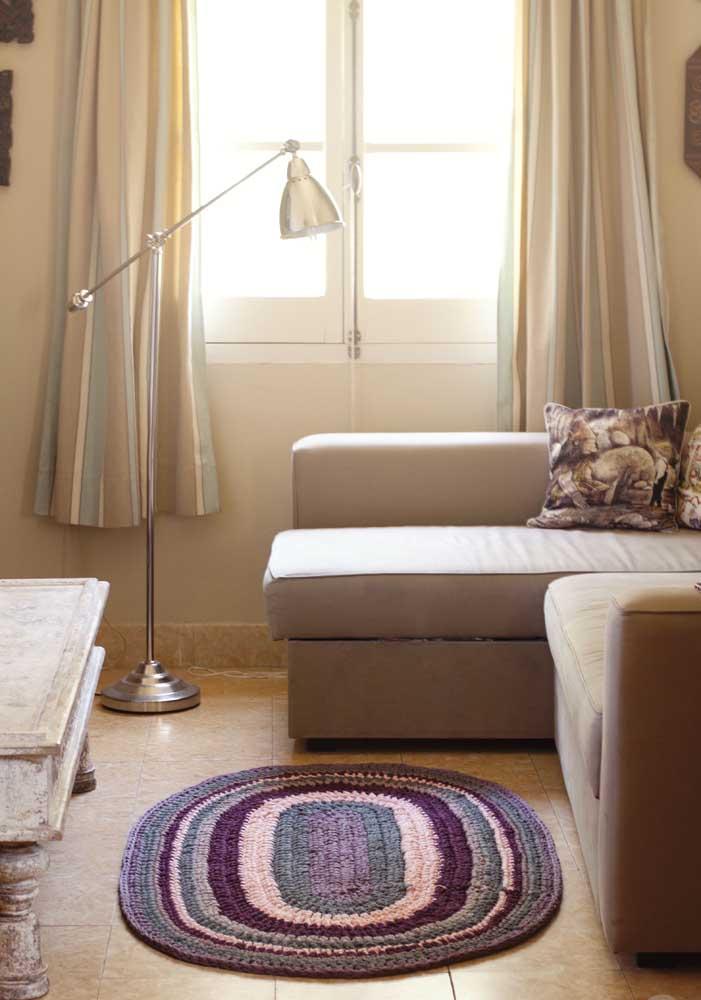 A sala de tons neutros ficou mais charmosa com o tapete de crochê oval rosa claro e roxo