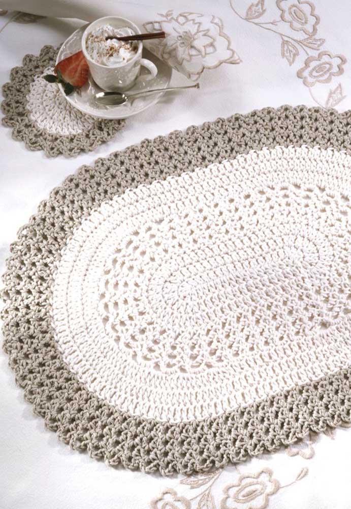 Tapete de crochê oval branco com bordas cinza; repare na delicadeza do porta xícaras no mesmo estilo do tapete