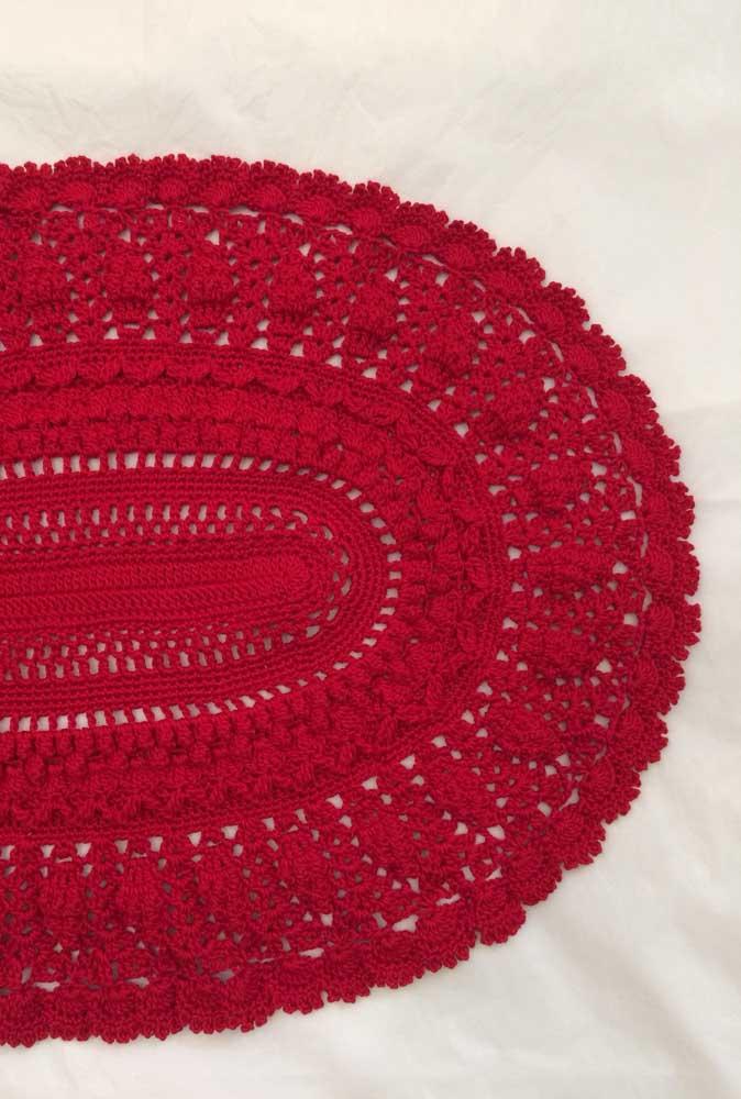 Um belo e grande tapete de crochê oval vermelho
